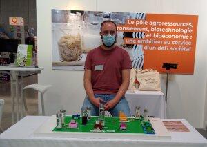 Julien présente une maquette lego du circuit des produits biosourcés. - © IC - Campus Matin